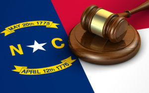 North Carolina US state law, code, legal system and justice concept with a 3d render of a gavel on the North Carolinian flag on background.